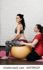 Midwife showing relief positions to a pregnant woman using a birthing ball