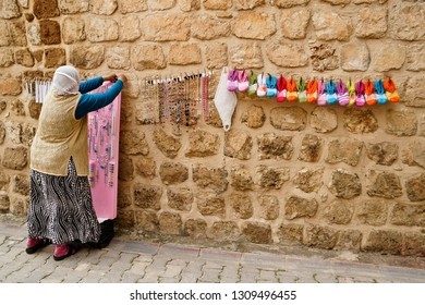 MIDYAT, TURKEY — MAY 5, 2011. A woman in traditional clothing and with her head covered displays handmade jewelry and crocheted items for sale on a stone wall in Eastern Anatolia.