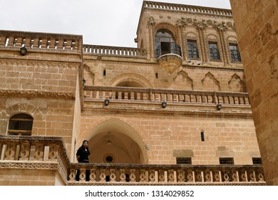 MIDYAT, TURKEY — MAY 5, 2011. A woman stands on the balcony of an elegant sandstone house on a cloudy day in Eastern Anatolia.