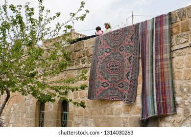 MIDYAT, TURKEY — MAY 5, 2011. A woman and child stand on the roof of a traditional stone house, its wall draped with drying carpets, on a cloudy day in Eastern Anatolia.