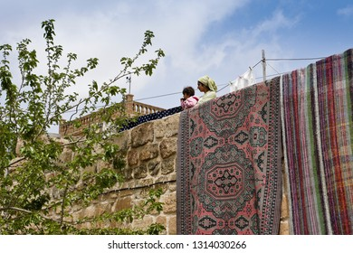 MIDYAT, TURKEY — MAY 5, 2011. A woman and child stand on the roof of a stone house, its wall draped with drying carpets, on a sunny spring day in Eastern Anatolia.