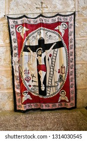 MIDYAT, TURKEY — MAY 5, 2011. A religious painting of Christ being crucified hangs on a stone wall at Deyrulzafaran Monastery in Eastern Anatolia.