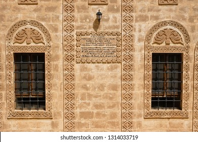 MIDYAT, TURKEY — MAY 5, 2011. Intricate carvings and a plaque with Aramaic script decorate the stone facade and windows of a building at Deyrulzafaran Monastery in Eastern Anatolia.