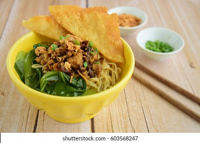 Mie Ayam or chicken noodle, Indonesian cuisine. Yellow wheat noodle topped with chicken meat, mushroom, bok choy. Served with fried wonton, scallion and fried shallot.