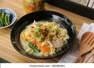 Mie Godog Jawa. Popular Javanese comfort food of yellow noodles with chicken, meatballs, vegetables and duck egg in chicken broth. Accompanied with cucumber pickles and green chili peppers.