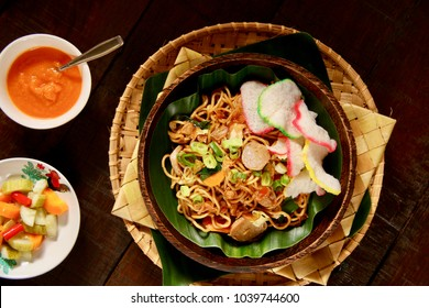Mie Goreng Jawa. Stir-fried egg noodles with cabbage, carrot, meatballs, chicken, and sweet soy sauce. Served with  tapioca crackers, chili sauce and cucumber pickles.