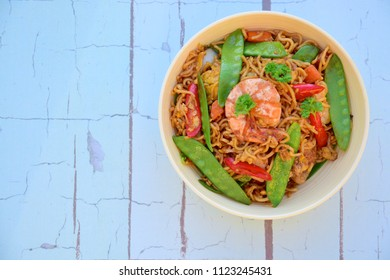 Mie goreng, traditional Indonesian fried egg noodle with prawn, snow pea, carrot, egg and chili