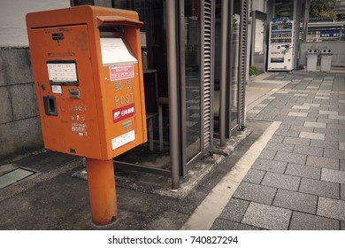 Mie, JP - OCTOBER 18, 2017: The old vintage orange postbox standing near a walkway in front of Uenoshi Railway Station.