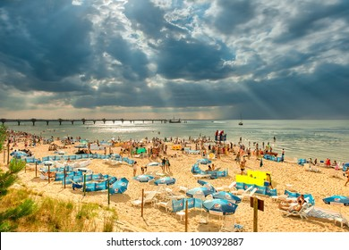 Miedzyzdroje / Poland - 07.11.2011: Lots of people on the sandy beach sunbathing, swimming in the sea, relaxing. Stormy clouds on the sky, summer season,