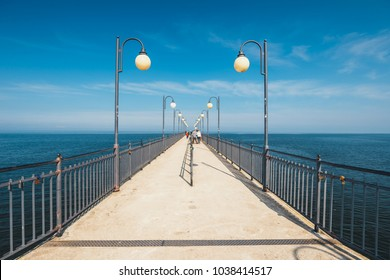 Miedzyzdroje, Poland - April 09, 2016: People walking on a concrete pier in Miedzyzdroje. Town and a seaside resort in Poland on the island of Wolin