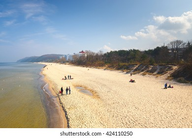 Miedzyzdroje, Poland - April 09, 2016: Unidentified people walking on the beach. Miedzyzdroje  is a major health-spa and tourist resort destination.
