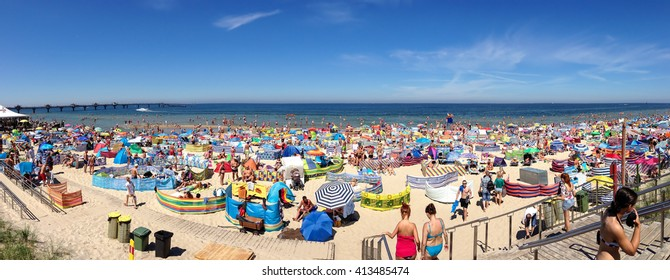 Miedzyzdroje, Poland July 19 2014: Unidentified locals and tourists relax on a colorful, crowded beach at Poland's Baltic sea resort of Miedzyzdroje.