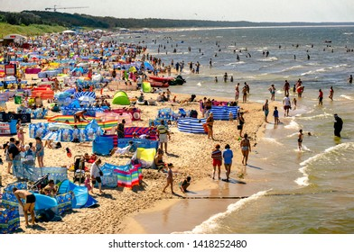 "Miedzyzdroje, Poland - July 20, 2018: View of the beach in ""Międzyzdroje"", Poland, near the Stars Promenade. Tourists, sunbeds and umbrellas on summer hot day. Strong wind at the sea, lots of tourists"
