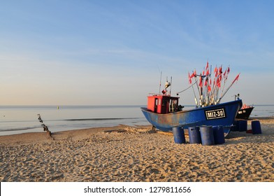 Miedzyzdroje, Poland, November 2018: Blue fishing boat on the sandy beach on the Baltic Sea.