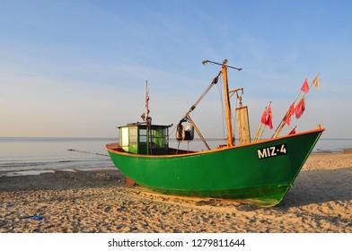 Miedzyzdroje, Poland, November 2018: Green fishing boat on the sandy beach on the Baltic Sea