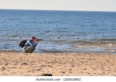 Miedzyzdroje, Poland, November 2018. professional photographer taking pictures on the beach