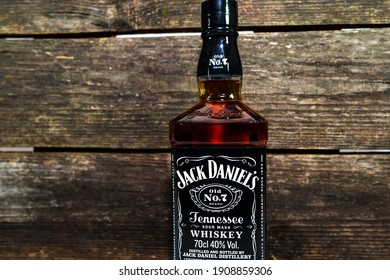 Miercurea Ciuc, Romania- 03 February 2021: Bottle of Jack Daniel's whiskey against dark aged wood boards, space for text.