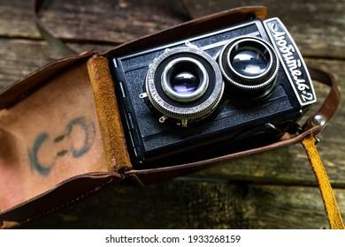 Miercurea Ciuc, Romania- 10 March 2021: Vintage soviet 35 mm film camera on weathered pine wood boards.