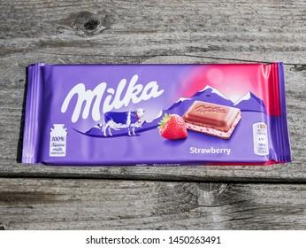 Miercurea Ciuc, Romania- 14 July 2019: Milka strawberry chocolate on aged old wood table.