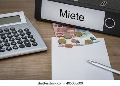 Miete (german Rent) written on a binder on a desk with euro money calculator blank sheet and pen