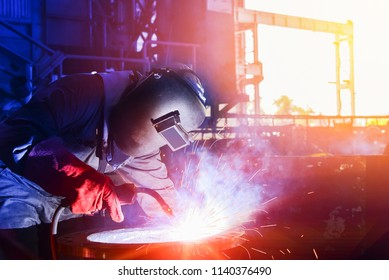 Mig welder man working process success with steel pipe on sparks light wear protective equipment and mask isolated on dark tone background