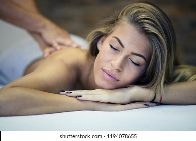 I might fall asleep this is so relaxing. Woman at a massage in spa center. Close up. Copy space. . Focus is on woman.