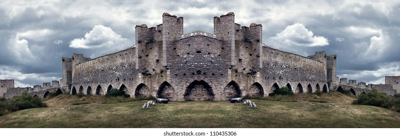 Mighty medieval city wall defence in panorama with dramatic colors and sky.