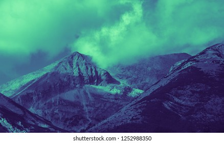 Mighty mountains, calm night alpine landscape, fall season. Clouds touch the mountain peaks.