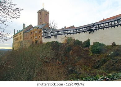 Mighty old castle Wartburg in Eisenach is a high watchtower with half-timbered walls on cliff among winter forest. UNESCO world heritage site, one of best german medieval fortresses.