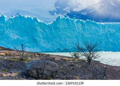 Mighty turquoise ice of Perito Moreno glacier and a tiny tourist ship on the right. Los Glaciares national park, Argentina
