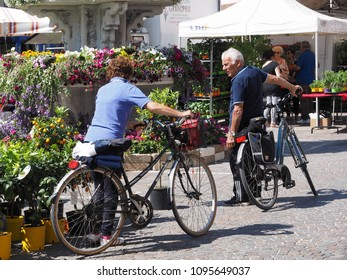 Migliarino, Italy - May 20, 2018. Fiera del fiore, Flower Fair. Buyers with a bicycle choose plants and flowers to buy.