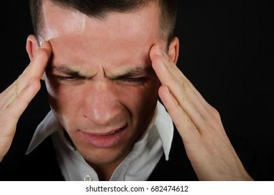 Migraine. Attractive guy. Black background.