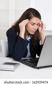 Migraine or burnout - overworked businesswoman massaging forehead at desk