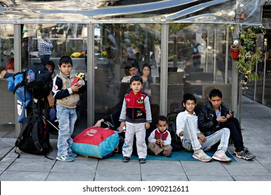 A migrant woman sits with children on November 13, 2015 at the Victoria square in central Athens, where hundreds of migrants and refugees stay temporarily.