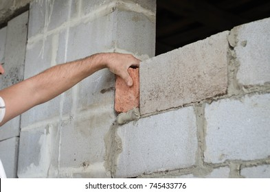 Migrant worker building cinder block wall in desert setting