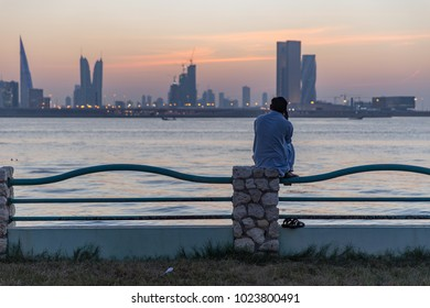 A migrant worker makes a phone call while watching the sun set over Manama, Bahrain.  October 1, 2017.
