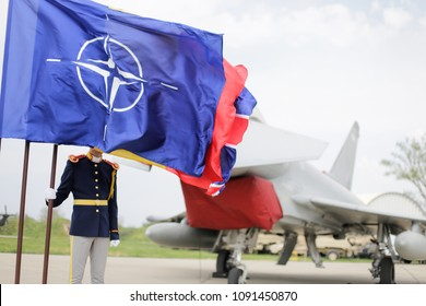 MIHAIL KOGALNICEANU, ROMANIA - APRIL 27, 2018:A romanian guard can be seen behind NATO, UK and Romania flags, while a Royal Air Force Eurofighter Typhoon fighter jet is presented to the press.