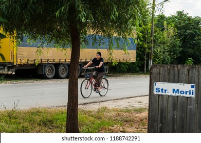 Mihail Kogalniceanu, Romania, September 5, 2018: Village transportation/Old woman riding a bike on a village street is passing by a lorry as seen between a fence and a tree.