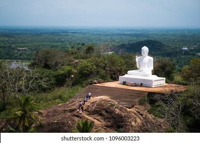 Mihintale, Sri Lanka - 07 May 2018: Big white Buddha statue against blue sky in Mihintale, the cradle of buddhism at Sri Lanka