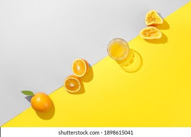 Miinimal orange juice flat lay. Fresh orange and glass of juice on trendy colors gray and yellow background. . Creative breakfast top view