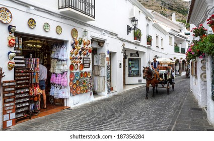 MIJAS, SPAIN - JULY 12, 2013: Shopping street in the city center, Mijas, Spain. Typical Andalusian white-washed village, located on a mountainside about 1,476 ft. above sea level.