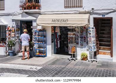 MIJAS, SPAIN - JUNE 1, 2018: Traditional souvenir in shop at Constitution Square (Plaza de la Constitucion) in picturesque White Mountain village of Mijas. Costa del Sol, Malaga province, Andalusia.