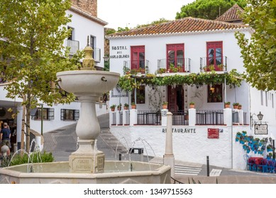 MIJAS, SPAIN - SEPTEMBER 27, 2019. Charming white village street lined with cafes, restaurants and souvenir shops - Mijas, Andalusia, Spain.