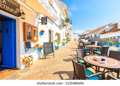 MIJAS TOWN, SPAIN - MAY 9, 2018: Street with restaurants and bars in picturesque village of Mijas, Andalusia. Spain is second most visited by tourists country in Europe.