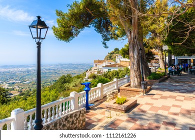 MIJAS VILLAGE, SPAIN - MAY 9, 2018: Restaurant terrace in picturesque white village of Mijas, Andalusia. Southern Spain is famous for mountain villages with white architecture.