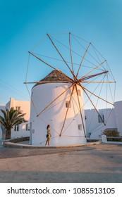 Mikonos Greek windmill during sunset Mykonos Greece, Young woman watching sunset