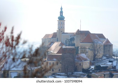 Mikulov castle at the winter covered in snow with smooth light blue sky , south moravia czech republic , touristic destination , view from the   kozi hradek  -  Goat hill