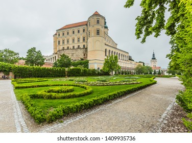Mikulov, Czech Republic / South Moravia - May 28 2019: Mikulov castle with yellow and white facade standing on a rock, green lawn in a garden and sandy footpath. Grey overcast rainy day.