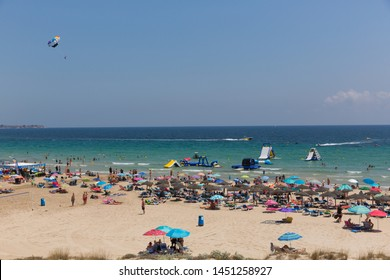 MIL PALMERAS, SPAIN-JULY 3rd 2019: Beautiful weather parasailing and beach water slides attracted visitors to the Costa Blanca playa at Mil Palmeras, Spain on Wednesday 3rd July 2019