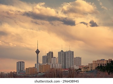 Milad Tower among high rise skyscrapers in the skyline of Tehran at dusk.